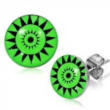 Kulaté puzetky z oceli - symbol slunce, zelené pozadí