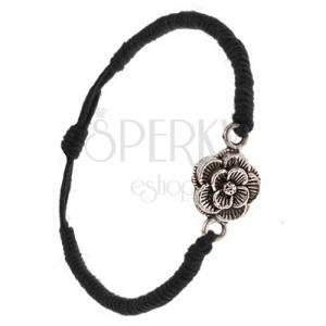 Náramek z černých šňůrek, hustě zaplétaný, patinovaný květ