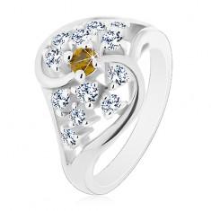 Lesklý prsten se zvlněnými rameny stříbrné barvy, čiré a zelené zirkony